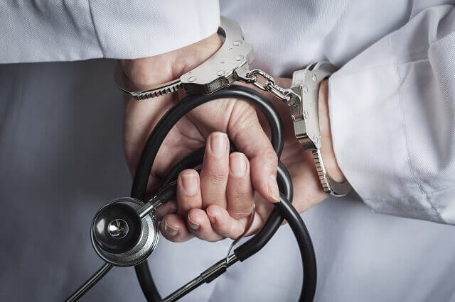 physician in handcuffs for health care fraud