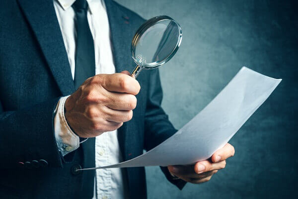 audit through magnifying glass