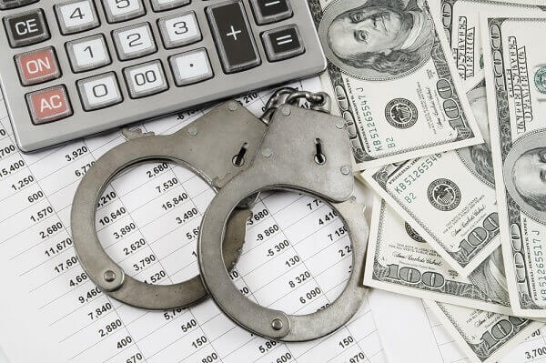 fraud: handcuffs, calculator, money